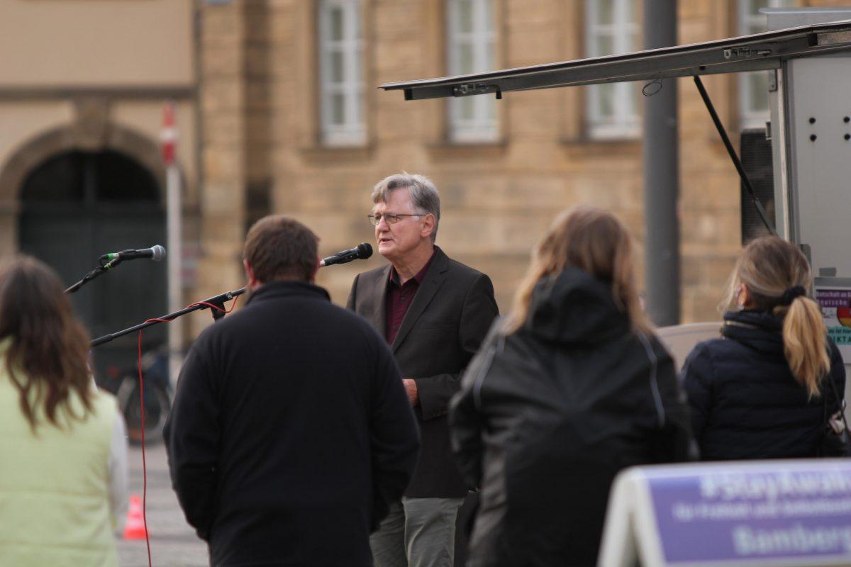 Lothar Mack steht am Mikrofon. Einige Menschen sind von hinten zu sehen und hören ihm zu.