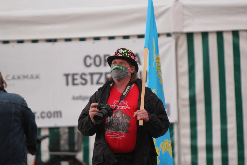 Ein Mann mit buntem Zylinder, rotem T-Shirt und blauer Flagge hält eine Kamera in der Hand.